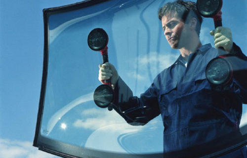 Mechanic carrying car window, view through glass